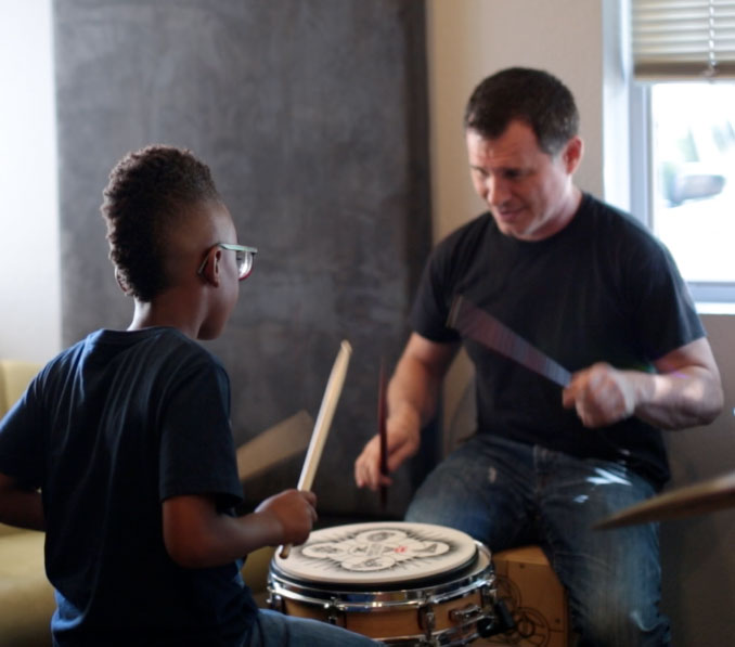 Music student practicing drums with music teacher