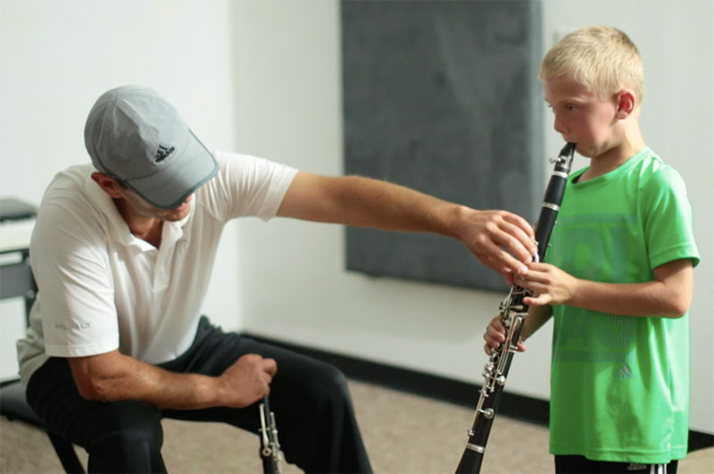 Music student practicing clarinet with teacher
