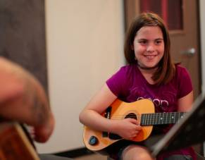 Girl receives guitar lessons