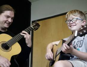 Boy receives guitar lessons