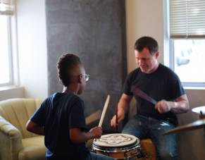 Boy receives drumming lessons