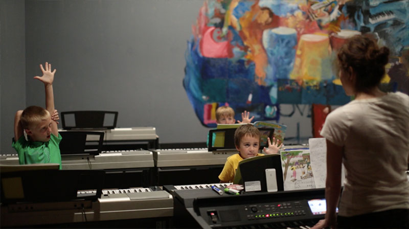 Three young boys learning piano in group keyboard class