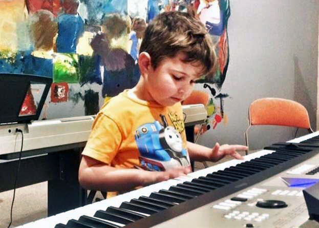 Young child practicing the keyboard in music class
