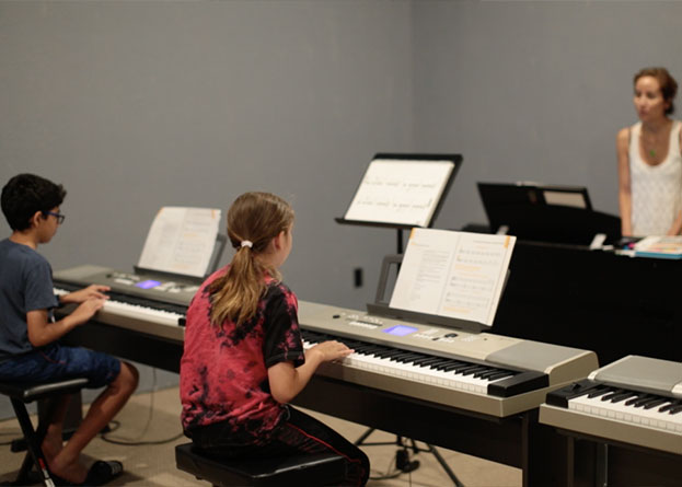 Two teens playing the electronic keyboard with the teacher watching