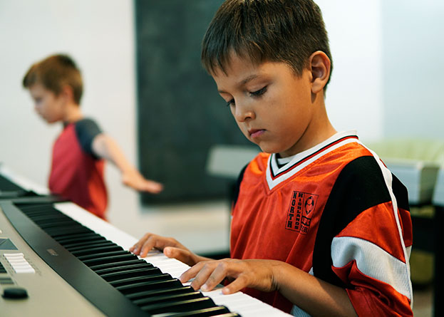 Two boys practicing the electronic keyboard in music class