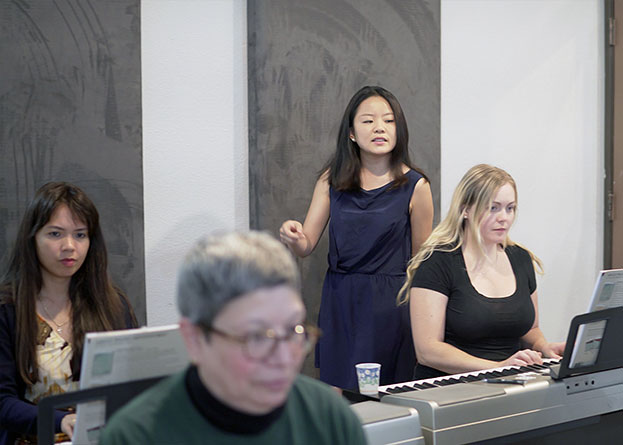 Three adult women playing the keyboard with their teacher observing