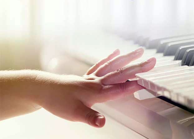 A young child pushing a key on a keyboard