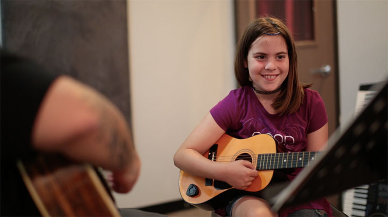 Young girl being taught to play guitar in private music lesson