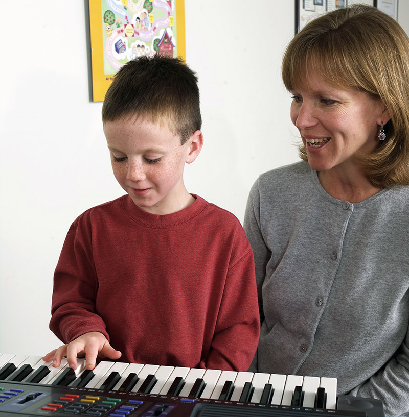 Mother helping her child with piano music practice