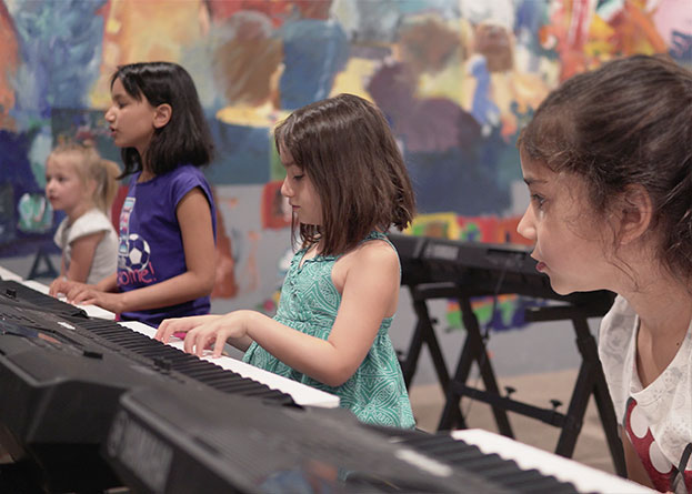 Four young girls in a keyboards music class